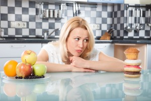 Woman choosing between fruits and cakes in the kitchen